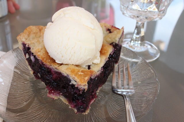 the best blueberry pie recipe with a scoop of vanilla ice cream on top