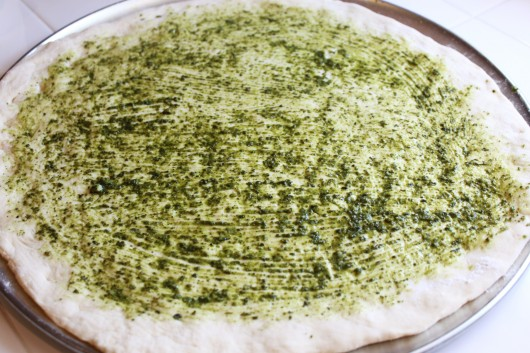 Pesto on pizza dough
