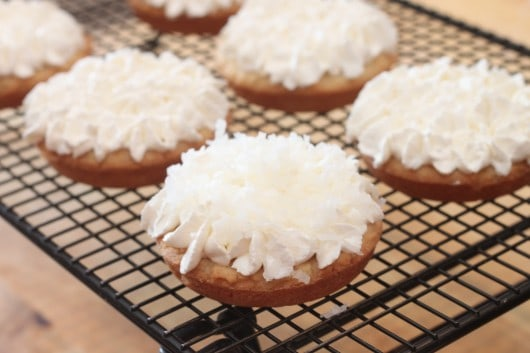 finished deep dish sugar cookies on cooling rack with white frosting and coconut flakes
