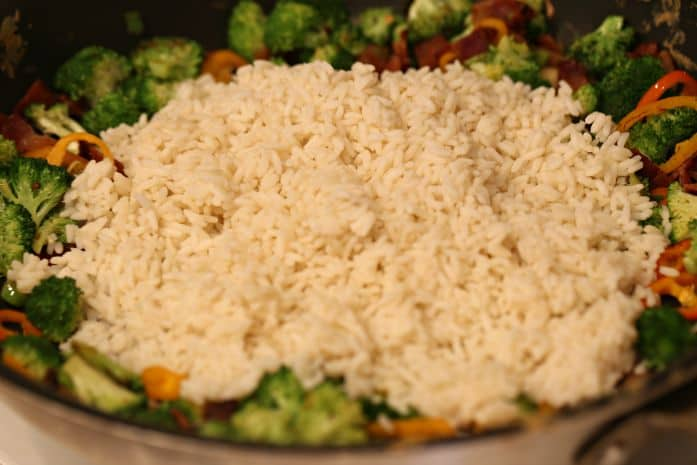 adding rice to vegetables for fried rice