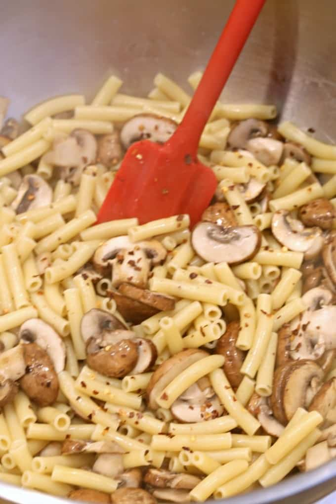 mixing sauce with pasta for mushroom baked ziti