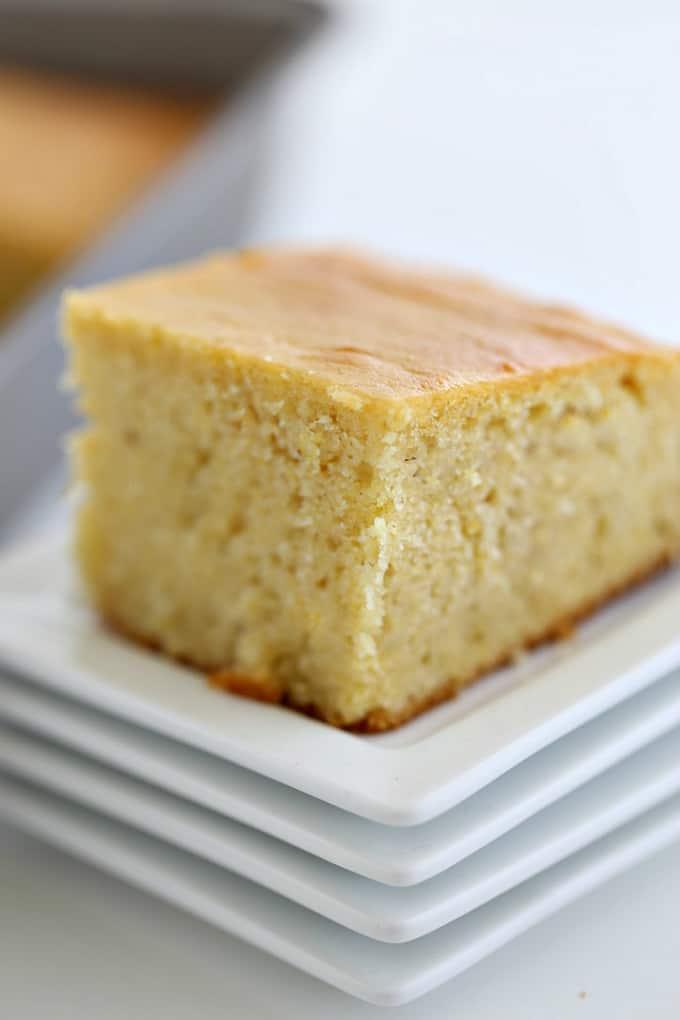 cornbread cut into a square on a stack of white plates