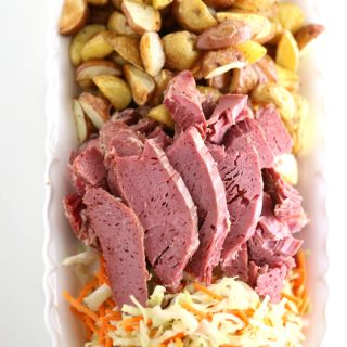 sliced slow cooked corned beef with roasted potatoes and sautéed cabbage