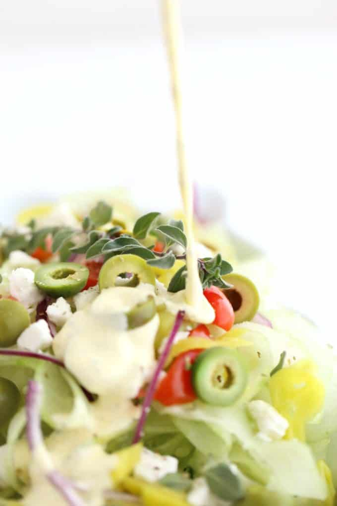 greek salad dressing drizzling onto salad www.createdbydiane.com