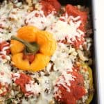 square baking dish with yellow and red stuffed peppers with cauliflower and ground beef topped with sauce and cheese