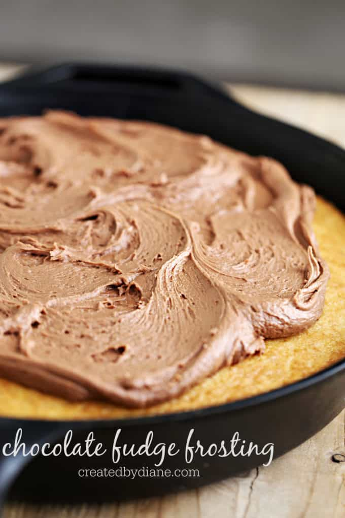 chocolate fudge frosting on a vanilla skillet cake in a cast iron skillet on a wood table