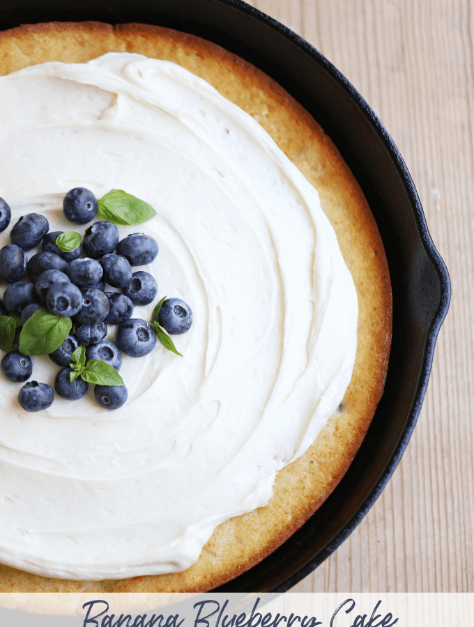 Banana Blueberry Cake in a skillet topped with cream cheese frosting createdbydiane.com