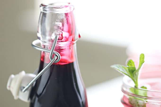 glass bottle with hinge lid full of bright pink hibiscus syrup
